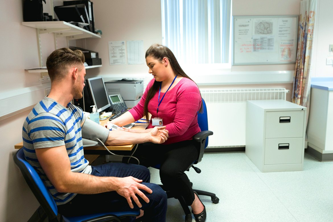 A female physician measures a young male patient's blood pressure.