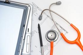 A stethoscope, stylus, two PDA tablets, and a printout stacked on a white background.