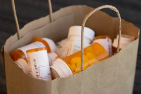 Paper bag filled with old prescription bottle and medication.