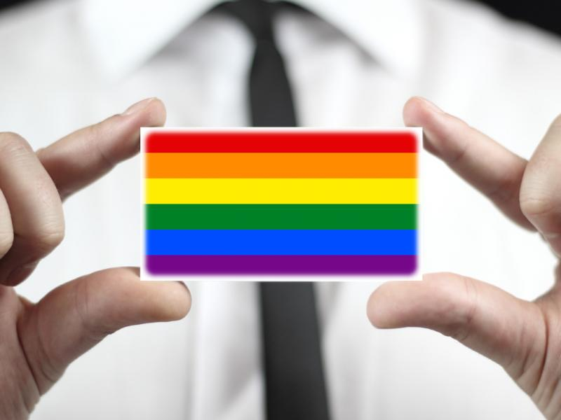 A close-up photo of a person holding a business card size rainbow.