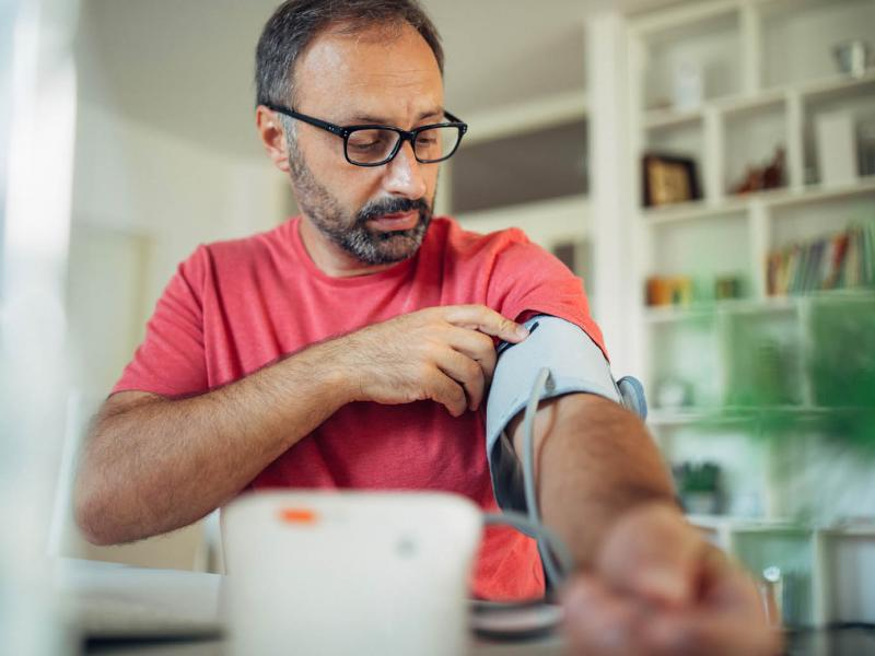 Man measuring his blood pressure at home