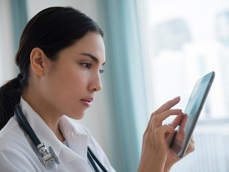 Physician on tablet reviewing information
