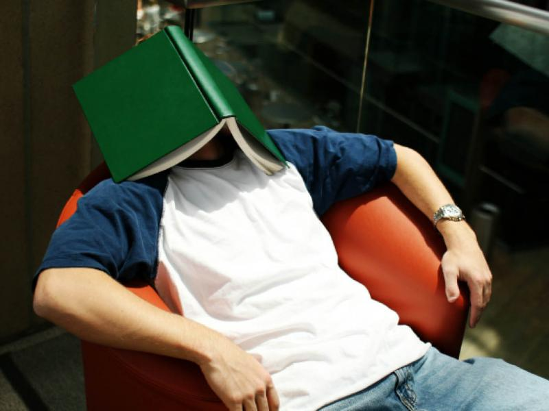 Student reclining in chair with book covering his face