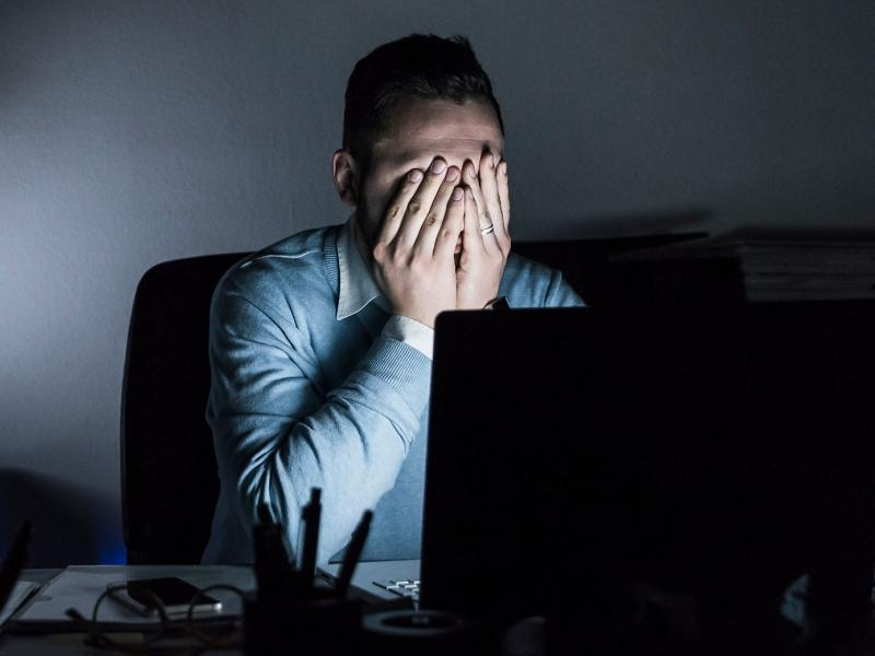 Exhausted man in front of laptop in dark room