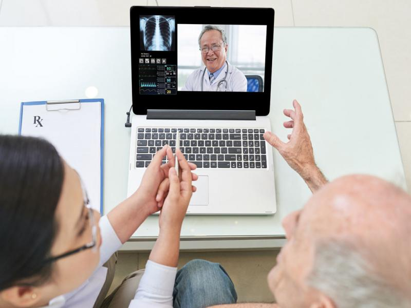 A physician consults with two patients through their laptop