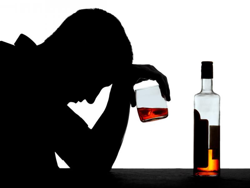 A silhouetted figure holding a glass of alcohol