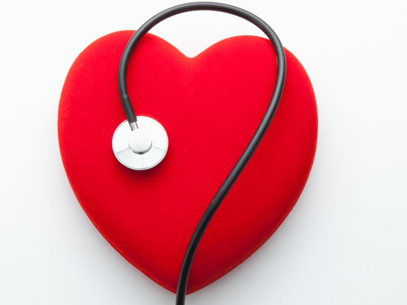 Stethoscope on top of red heart on white background