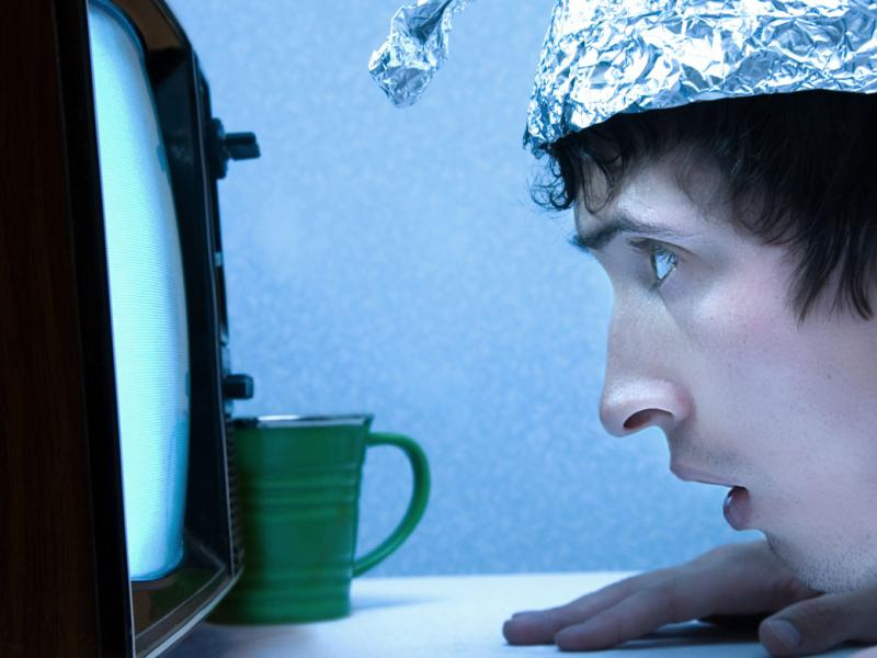 Man in tinfoil hat stares at TV screen