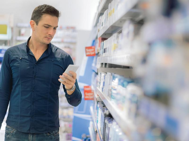 Man in pharmacy looking at a prescription