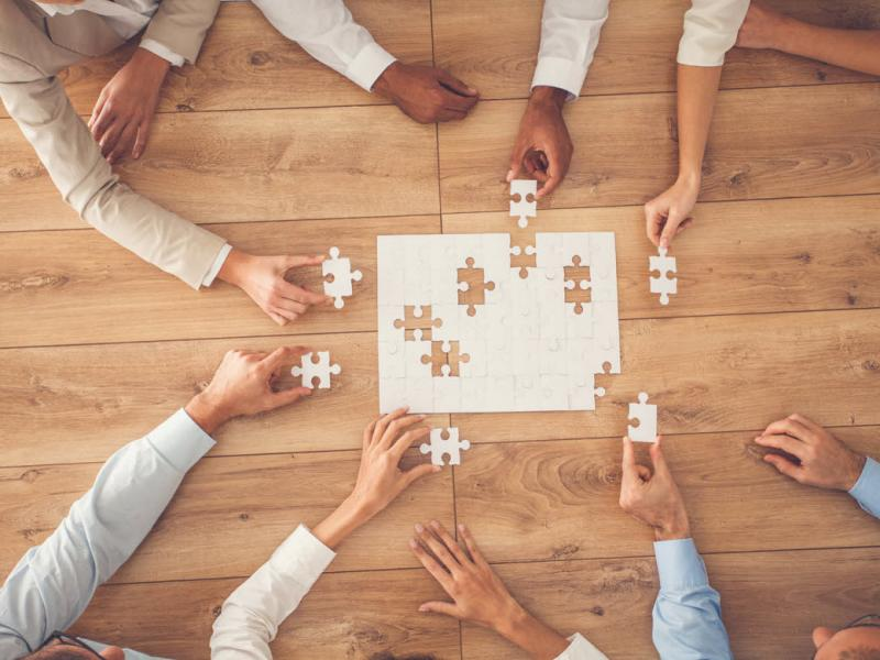 Tight shot of group of people sitting around a table working on a puzzle