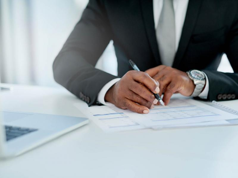 Man in a suit writing on a document