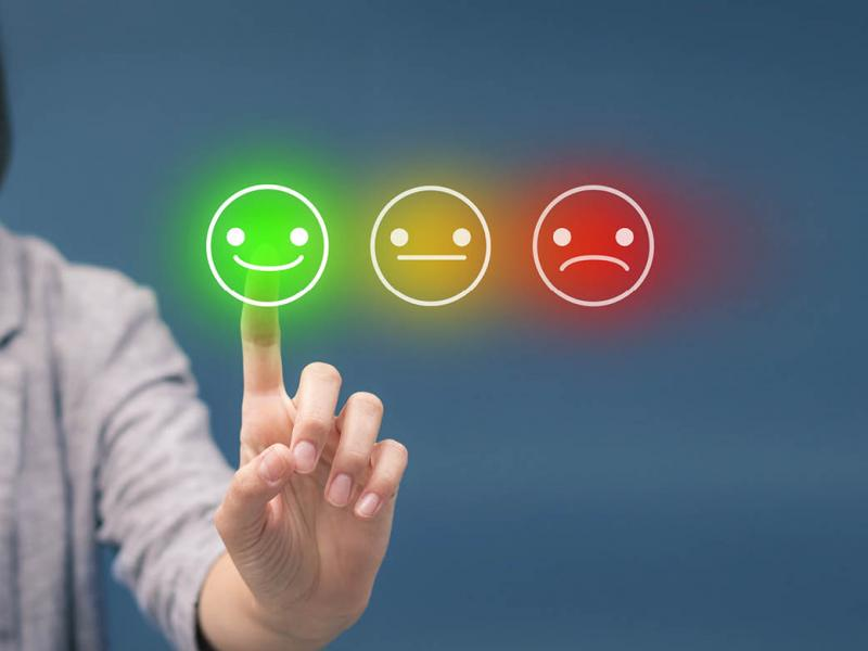 Person touching a screen of 'rate your satisfaction' smileys