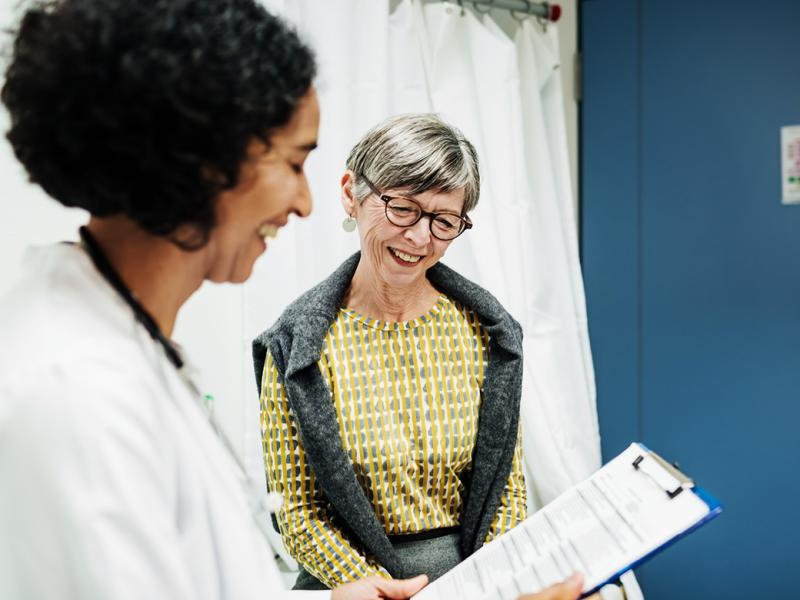 Smiling senior patient and physician reviewing patient chart
