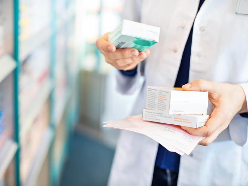 Tight shot of pharmacist reading text on prescription box