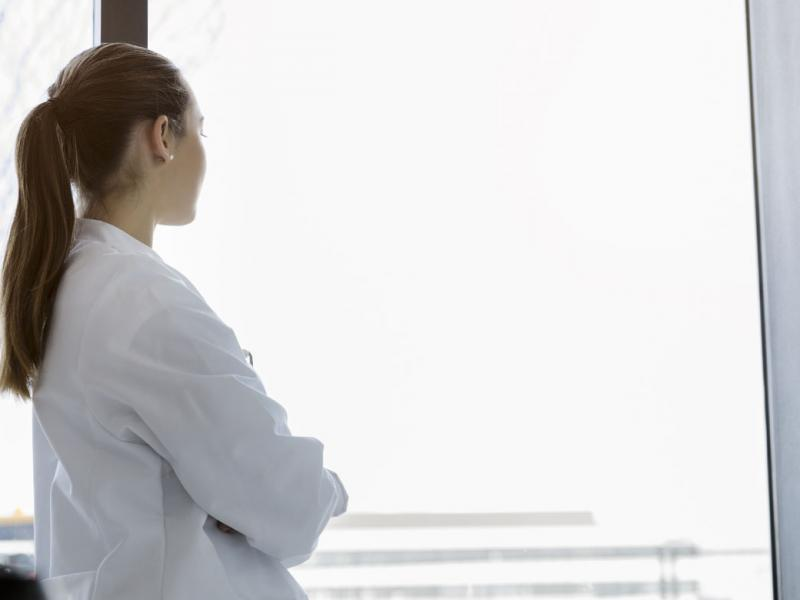 Woman physician looking out the window