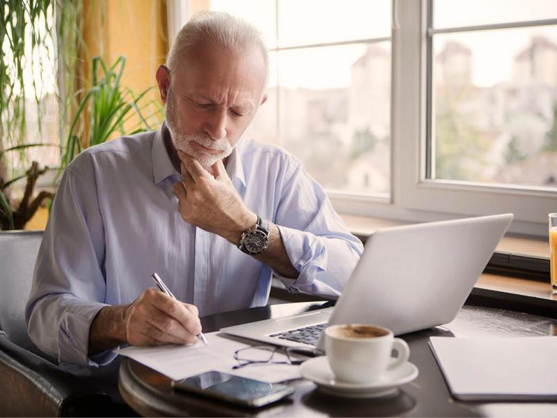 Man sitting in front of a laptop and writing a list