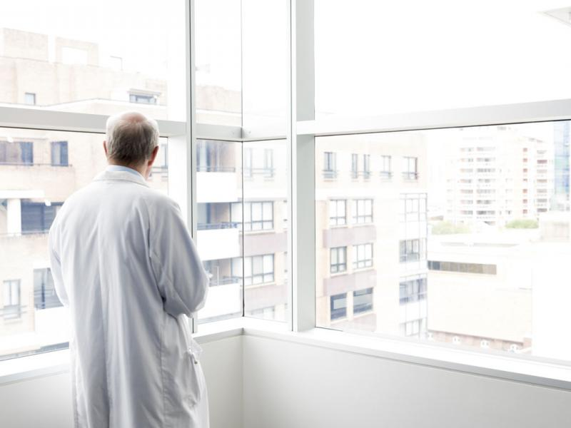 Physician standing alone and looking out a window