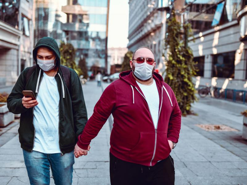Two people in facemasks holding hands