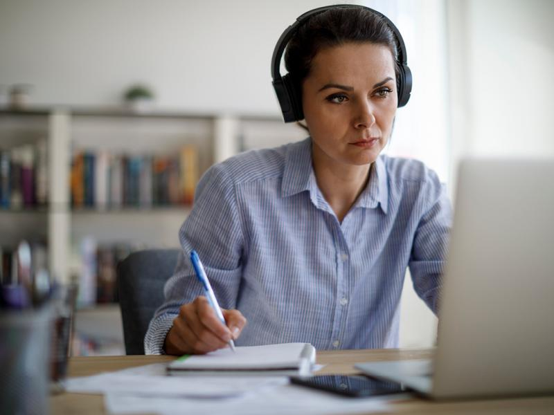 Person wearing headphones at a laptop