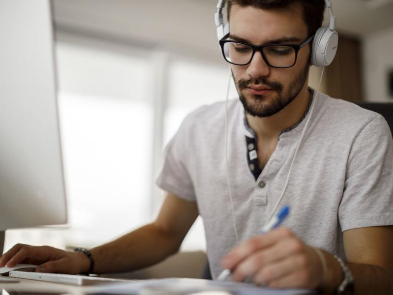 Man wearing headphones working at a computer, taking notes.
