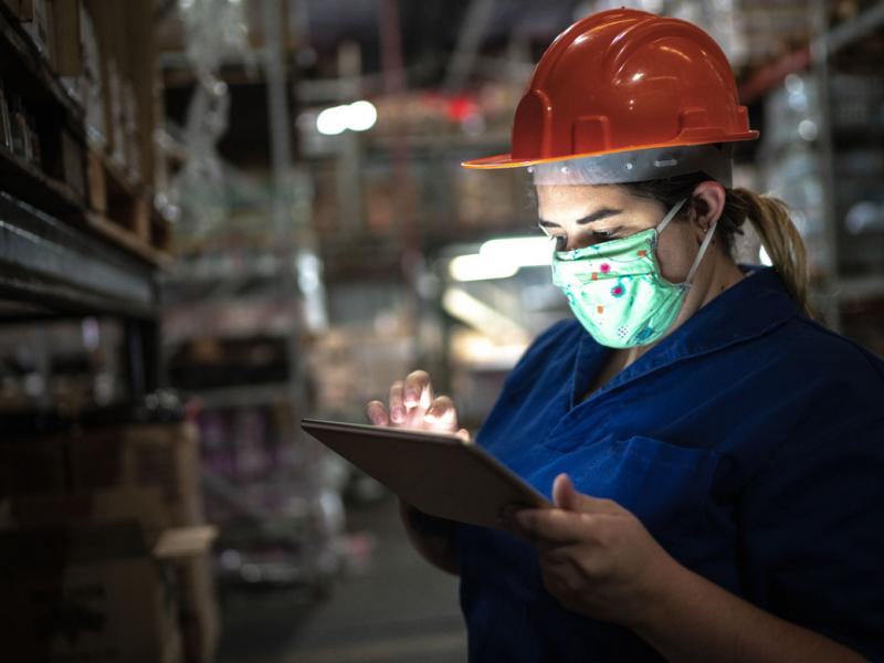 Warehouse worker wearing a face mask checking a smartpad.