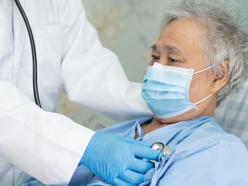 Patient wearing a face mask being examined by physician