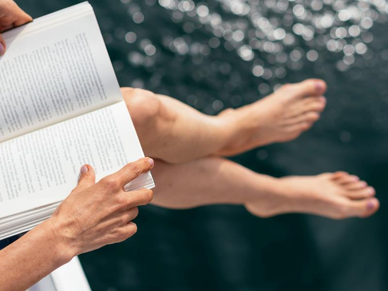 Close up of a book with the reader's legs and hands visible