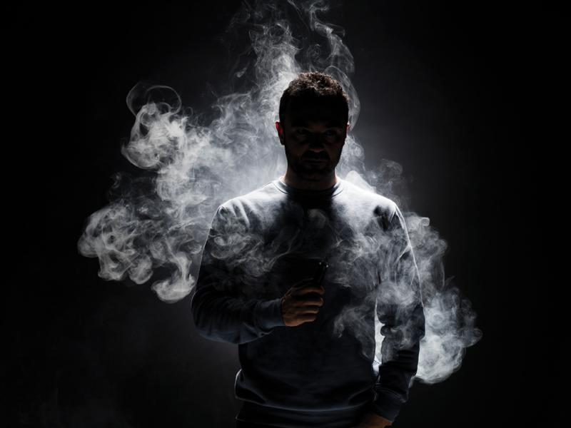 Human figure surround by smoke fragments on a black background.