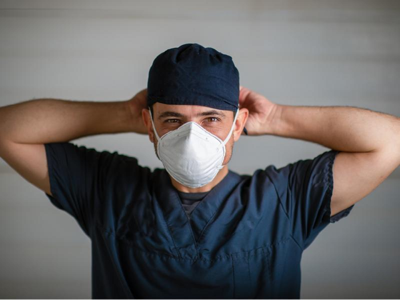Chest up view of a doctor in scrubs tying on a mask.