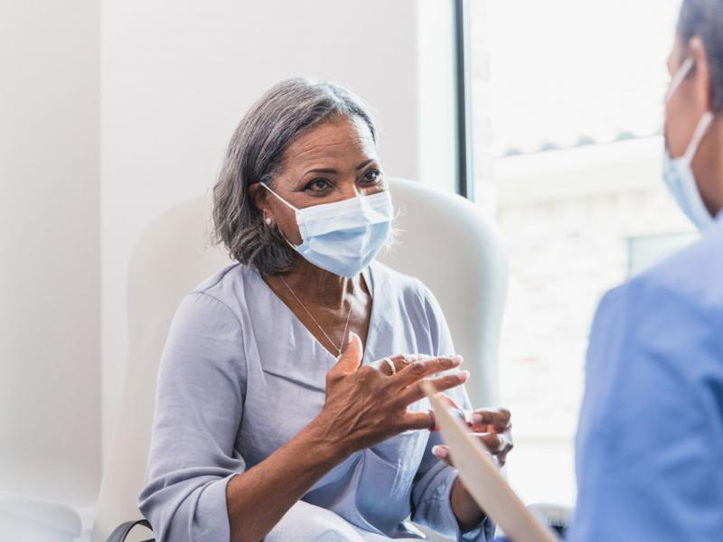 Woman patient with mask talking to physician wearing mask