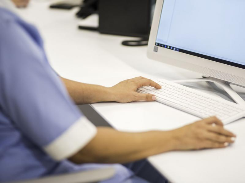 Health care worker at desk typing on keyboard_Tight shot of arms and hands