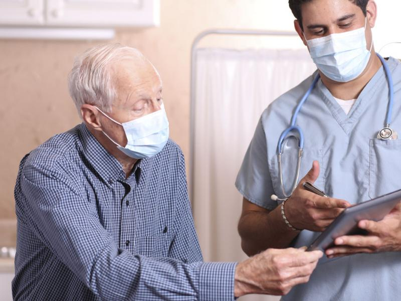 Physician and patient wearing masks and reviewing information on a tablet.