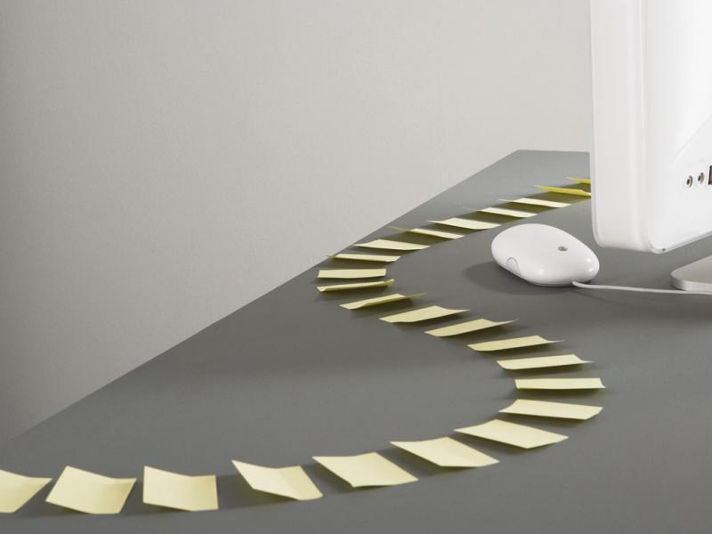 Trail of sticky-notes in an s-curve pattern leading to a computer.