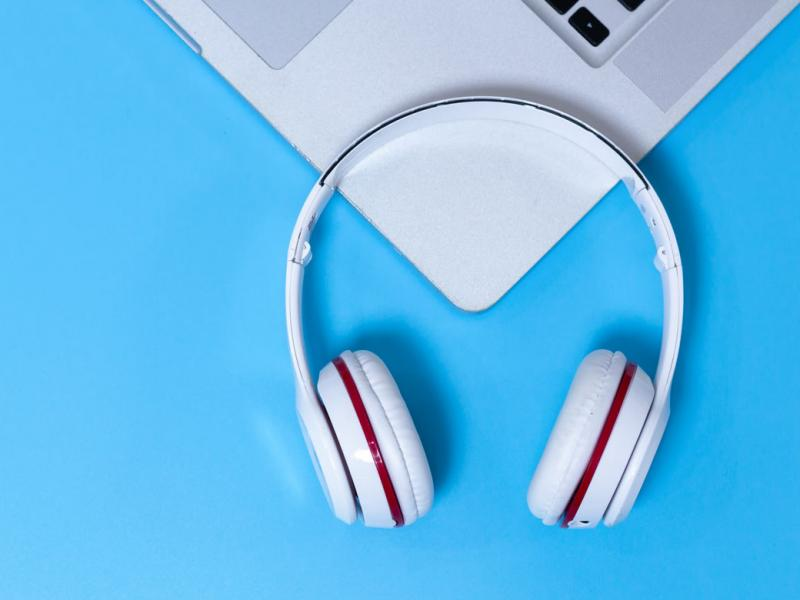 Laptop and headphones against blue background