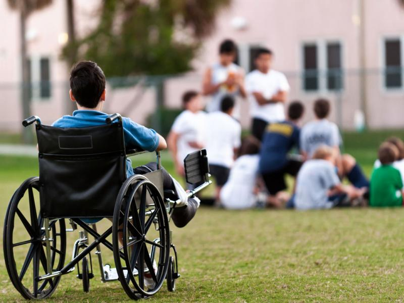A child in a wheelchair in the foreground looking at a group of children playing in the background.