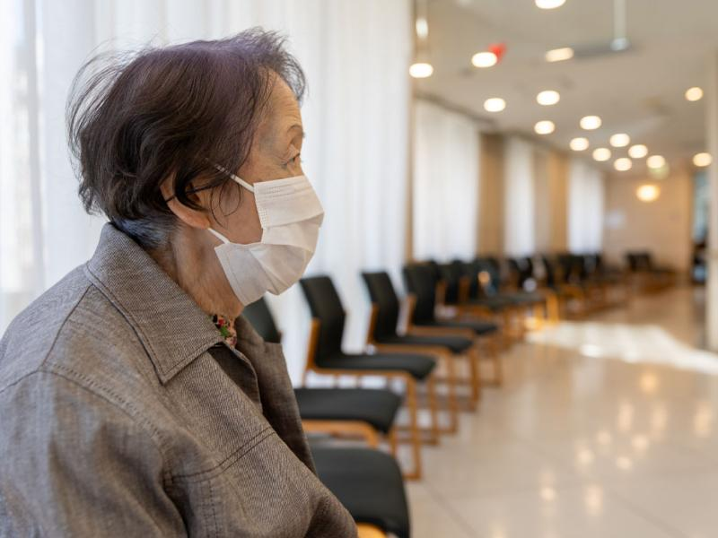 An older woman sitting alone in a hospital waiting room wearing a face mask.