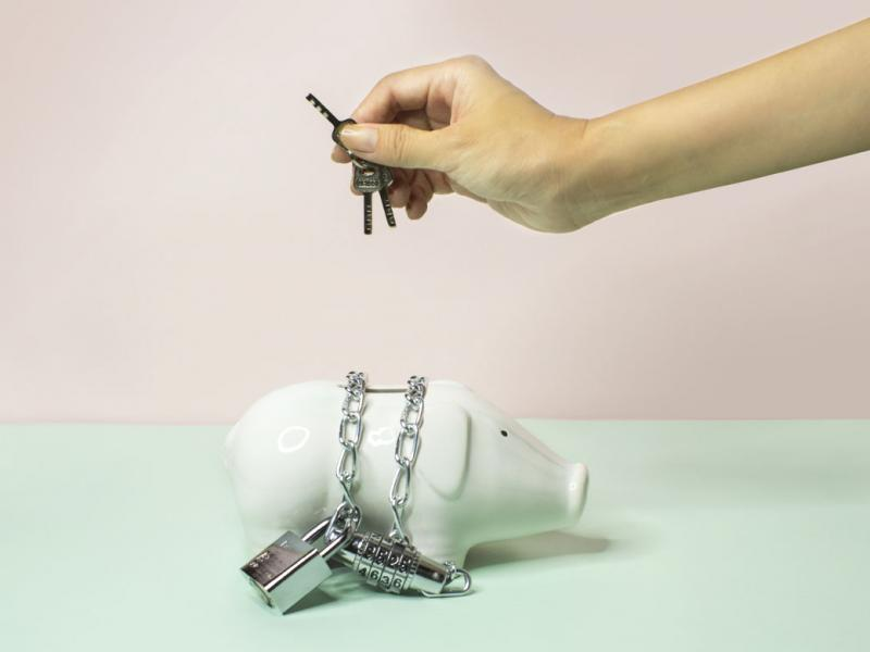 Person holding a key over a chained up piggy bank against a pastel pink and blue background