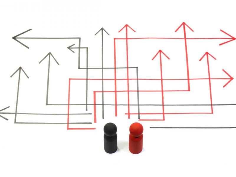 Two wooden block people, one black and one red, standing on a white background facing a number of paths represented by multiple, angular black and red arrows drawn in marker.