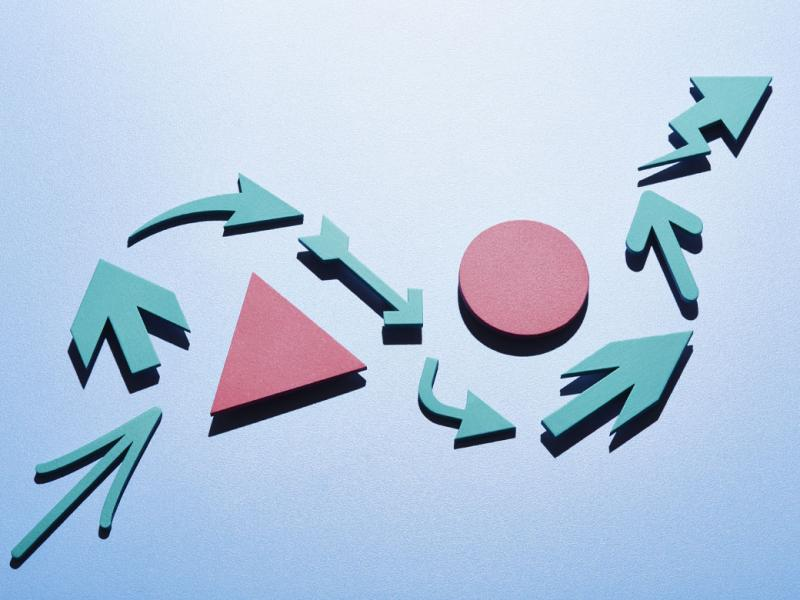 A series of light blue arrows of different shapes and design making an s-curve around a pink triangle and pink circle.