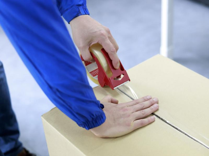 Close-up of a pair of hands taping a box shut.