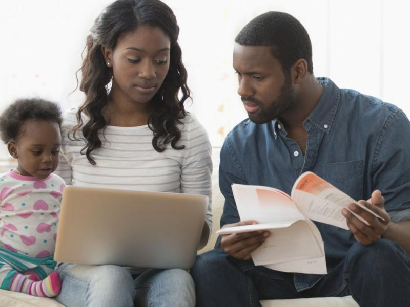 Family looking at a laptop and bills