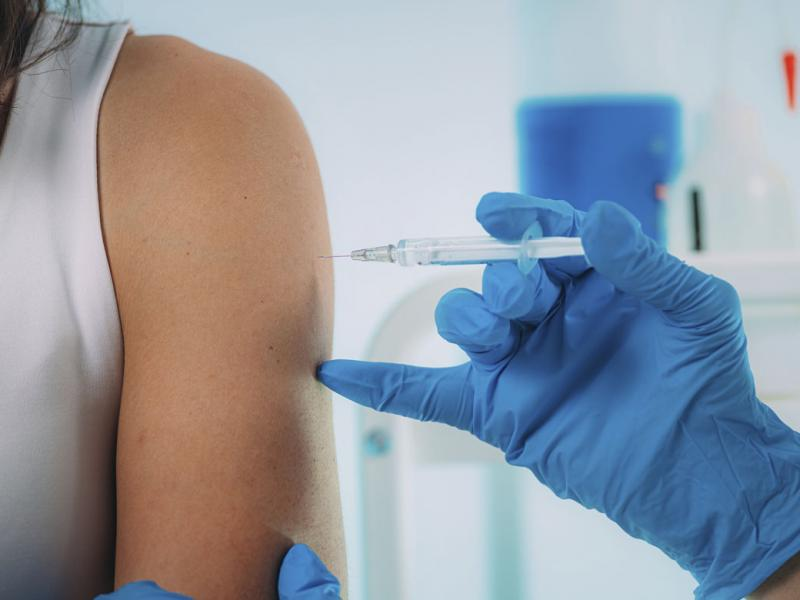 Close-up of a woman's arm and shoulder as she is being given a vaccination by a gloved hand.