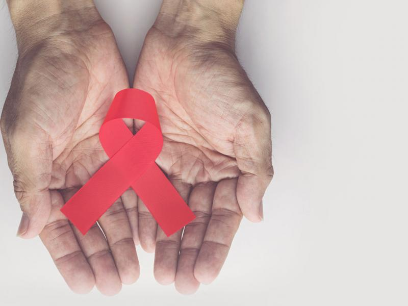 A pair of hands, palms up, holding a red AIDS ribbon against a white background.