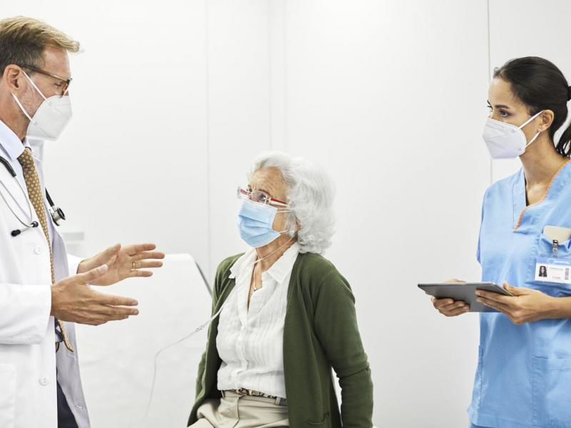 Health care workers speaking with patient