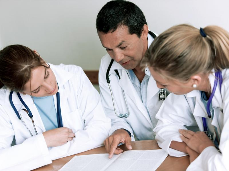A physician scans a document with 2 medical students.