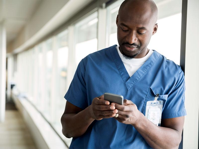 A young physician leans against a wall of windows and looks at his smart phone.