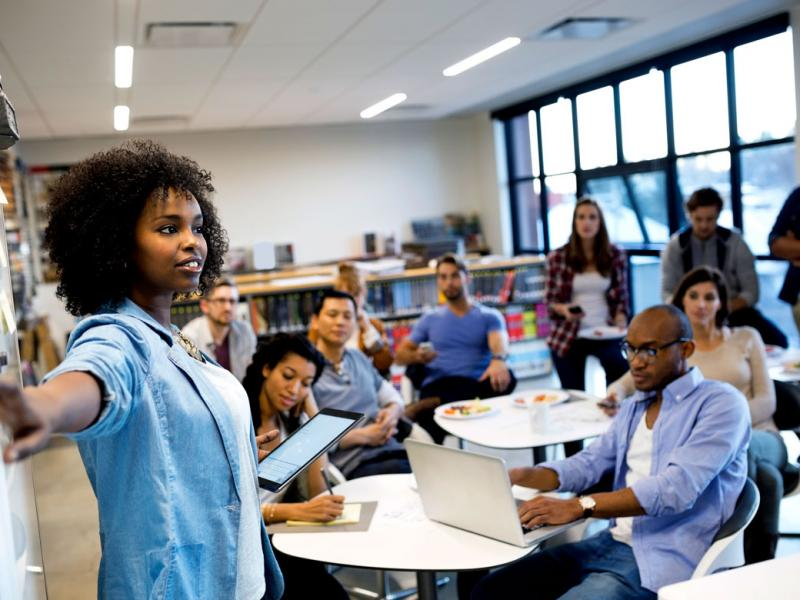 A classroom full of diverse medical students listens to one of their classmates as she explains a procedure using a whiteboard.