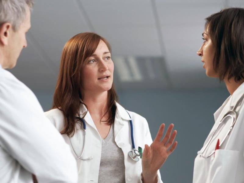 One male and two female physicians standing in a group while talking.