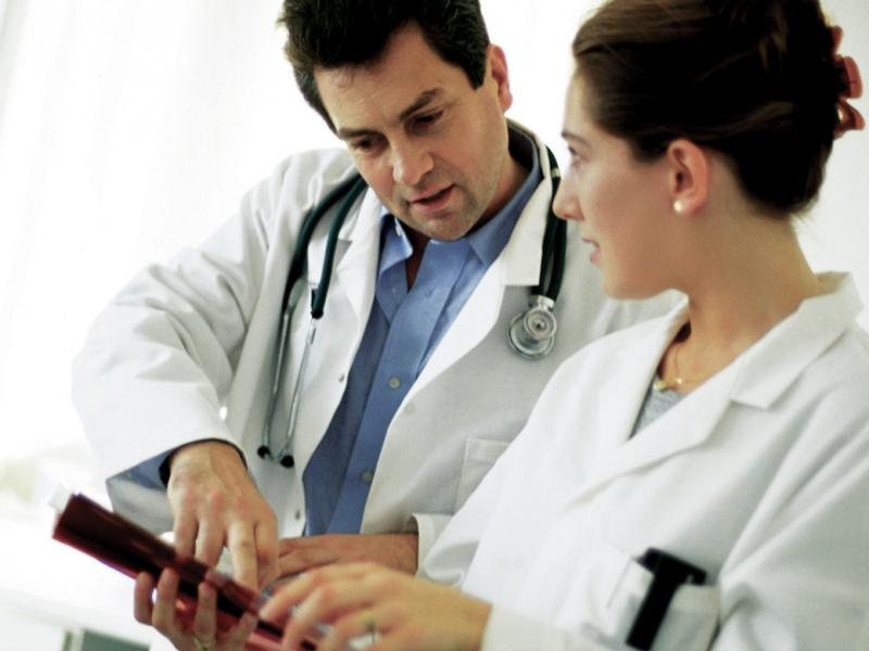 A man and a female physician look at the screen of a tablet.