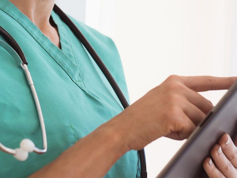 Close up of a physician using her tablet.